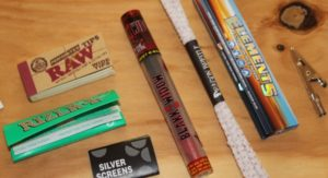 Rolling papers and items from Dollar High Club Primo Box