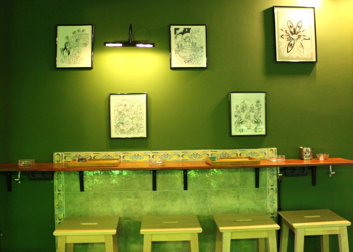 One of the seating areas with row of stools against the wall and small table